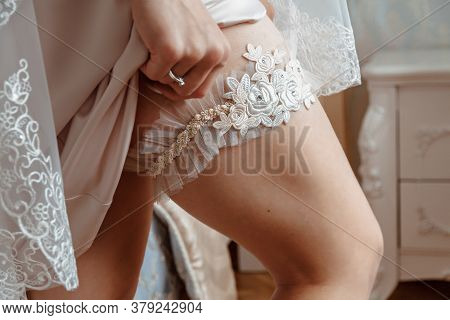 Bride Puts A Garter On Her Leg. Garter On The Brides Leg Close-up.