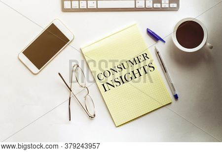 Consumer Insights Text On The Yellow Paper With Phone, Coffee, Pen