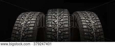 Three Studded Winter Tires Wheels In A Row On A Black Background, Panoramic Shot