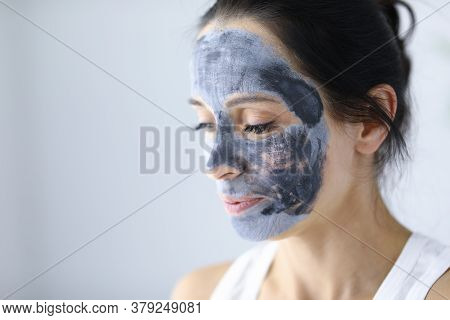 Womans Face Is Covered With Clay Cosmetic Mask For Skin Rejuvenation. Revitalizing Procedures For Fa