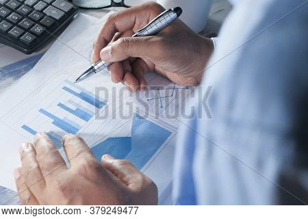 Rear View Of Man Hand With Pen Analyzing Bar Chart On Paper