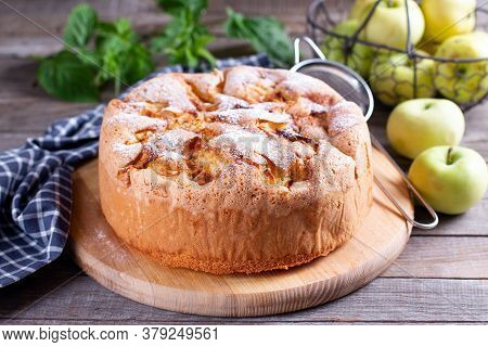 Sponge Cake With Apples On A Wooden Board On The Table. Homemade Pie