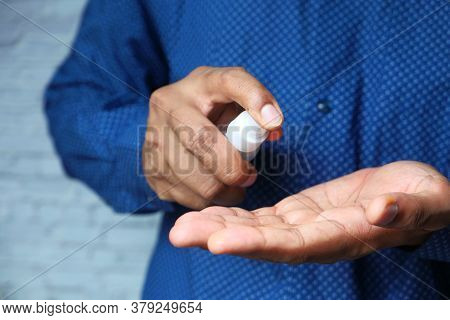 Close Up Of Young Man Hand Using Hand Sanitizer Spray.