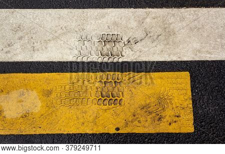 Close-up Of Car Tire Prints On The White And Yellow Stripes Marking The Pedestrian Crossing. Securit