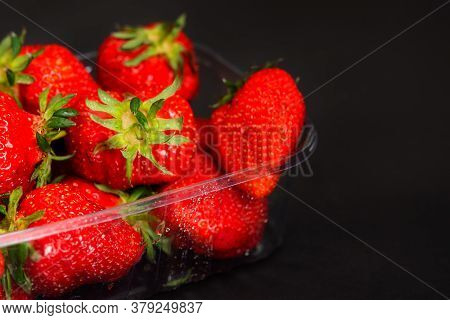 Strawberry Close-up In A Plastic Container On A Black Background. Fresh Juicy Strawberries In Select