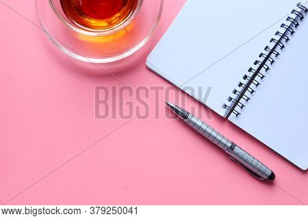 High Angle View Of Open Notepad On Pink Background