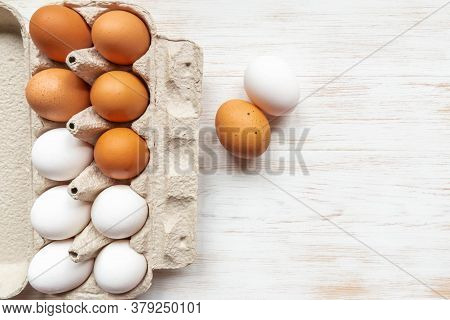 Brown And White Eggs In Recycled Cardboard Box And Two Chicken Eggs Near On Wood Table. Free-range O