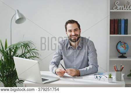 Smiling Handsome Young Bearded Business Man In Gray Shirt Sitting At Desk Working On Laptop Pc Compu