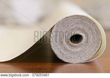 Unfolded Roll Of Light-colored Wall Paper On The Floor Close-up. The Concept Of Cosmetic Repairs In