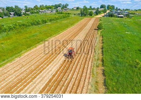 Rural Landscape Aerial View Of A Village On A Field With Plantings Of Vegetable Crops, Plowing Hilli