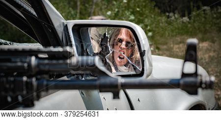 Abstract Mirror View Of Aggressive Female Soldier Shooting From Car