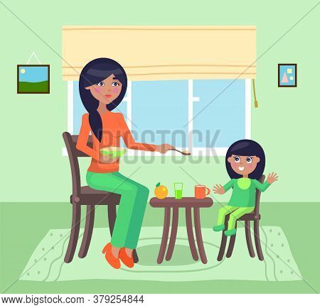 Young Mother Feeding Her Daughter Give Spoon With Poridge Or Meal Sitting At Table. Little Girl Smil
