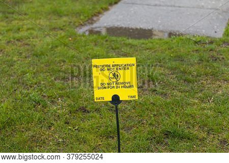 A Small Yellow Sign Is Placed On The Front Lawn Agter Chemical Pesticide Was Applied As A Warning To