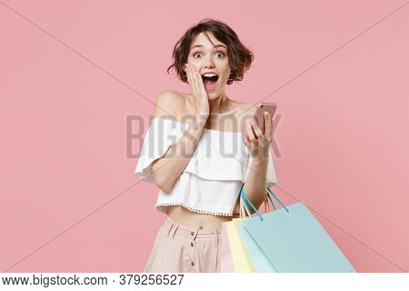 Shocked Young Woman Girl In Summer Clothes Hold Package Bag With Purchases Isolated On Pink Wall Bac