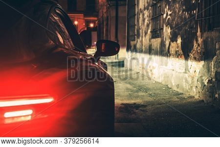 Automotive Theme. Exotic Car Night Drive In Dark Aged Urban Area Alley Close Up Photo.