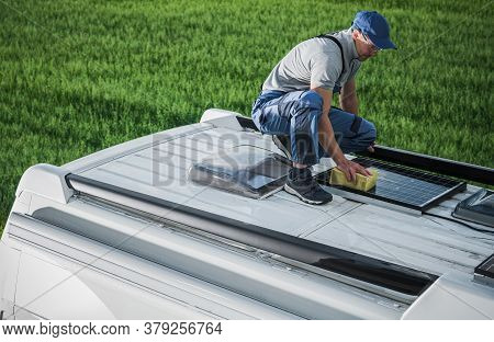 Caucasian Men In His 40s Cleaning Camper Van Rv Roof Installed Solar Panels Using Sponge And Soft Wa