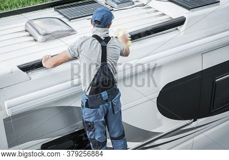 Recreational Vehicles Industry Theme. Caucasian Rv Service Worker Washing Camper Van Roof Using Larg