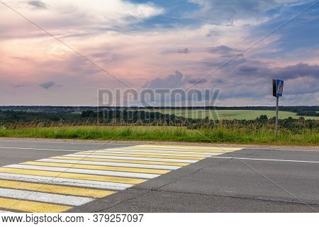Empty Suburban Paved Road With A Pedestrian Crosswalk Overlooking Green Fields And A Beautiful Sunse