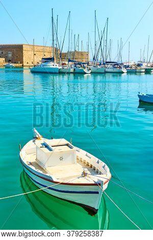 Small white fishing boat in the harbour near Koules Fortress in Heraklion, Crete, Greece. Greek scenery