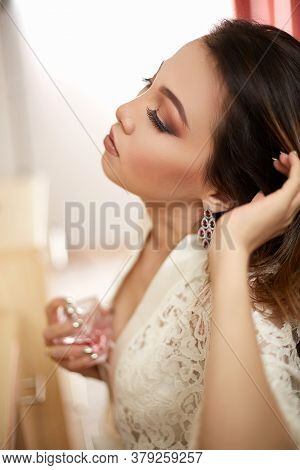 A Young Beautiful Asian Woman In A Beige Lace Dressing Gown Put On Morning Makeup And Scented With P