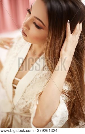A Young Beautiful Asian Woman In A Beige Lace Dressing Gown Put On Morning Makeup And Looks In The M