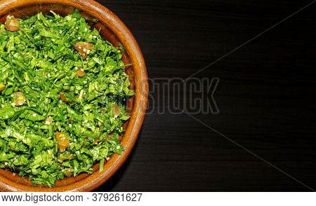 Famous Traditional Arabic Cuisine. Tabbouleh Green Salad In A Brown Bowl On Dark Wooden Background.