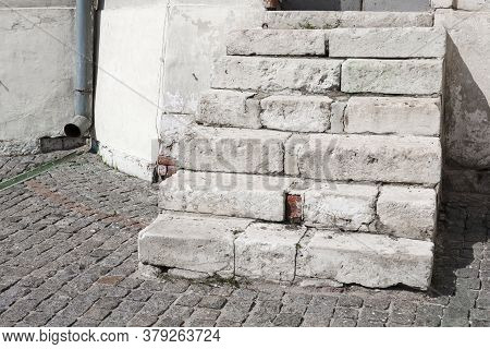 Ancient White Stone Steps On A Cobblestone Street