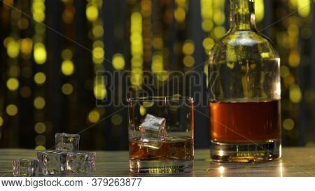 Golden Whiskey, Cognac Or Brandy In Glass With Ice Cubes And Bottle On Wooden Table. Shiny Gold Part