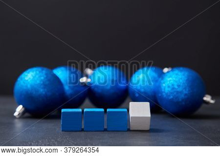 Festive Xmas Decor. Happy Holiday. New Year Concept. Wooden Cubes Placed In Line. Blue Balls With Gl