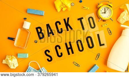 Text Back To School On Yellow Background With School Supplies, Protective Face Mask And Sanitizer An