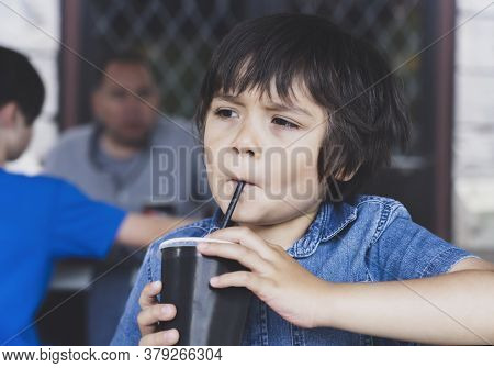 Cute Toddler Boy Drinking Cold Drink, Happy Child Sitting In Cafe Drinking Soda Or Soft Drink With A