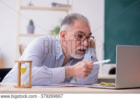 Old male teacher in the classroom