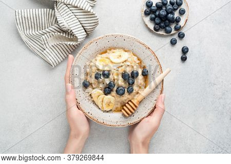 Female Hands Holding Bowl Of Oatmeal Porridge With Banana Slices, Blueberries, Coconut Flakes And Na