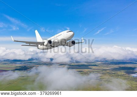 Commercial Airplane Flying Above Cloudscape In Day Toned Sun Light
