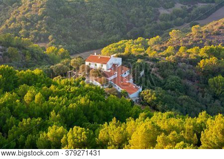 Traditional Spanish Houses With Red Roofs Surrounded By Trees. Menorca Island, Balearic Islands, Spa