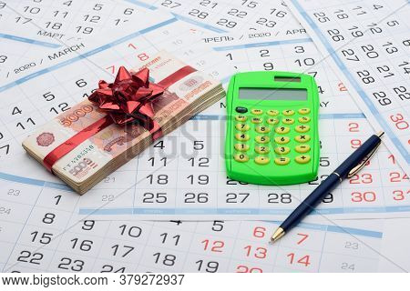 On The Background From The Calendar Lies A Bundle Of Money With A Red Bow, A Calculator And A Pen