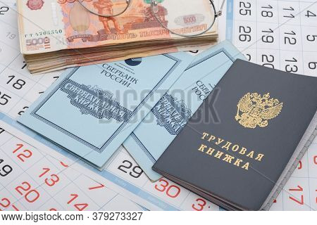 Anapa, Russia - 29.06.2020: On The Background Of The Calendars Lie A Work Book, A Savings Book, A Bu