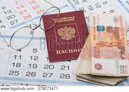 Glasses, Passport And A Bundle Of Money Are On The Sheets Of A Wall Calendar