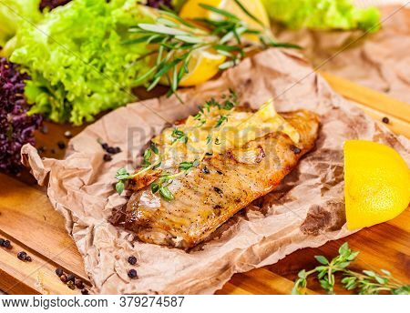 Baked Seabass Fillet With Herbs And Spices On Wooden Board