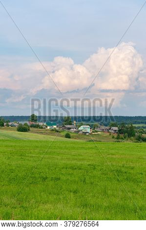 Field Of Green Grass With Wooden Farmhouses On A Hill And A Cloudy Sky. Rural Landscape