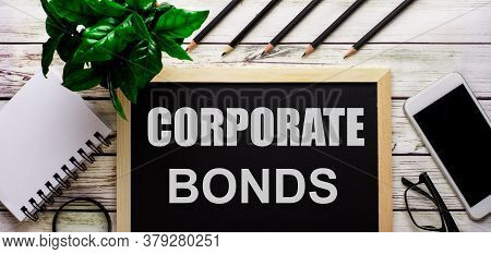Corporate Bonds Written On A Black Background Near Pencils, A Smartphone, A White Notepad And A Gree