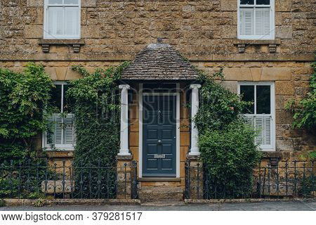 Facade Of A Traditional English House In Broadway, Cotswolds, Uk, Covered With Climber Plants.
