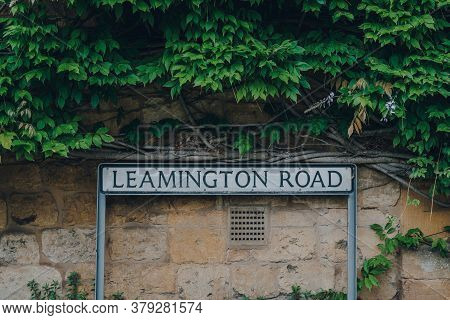 Close Up Of Leamington Road Street Name Sign Against The Limestone Cottage And Green Foliage In Broa