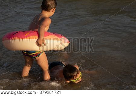 A 5-year-old Boy Swims In The Sea With A Donut-shaped Inflatable Circle With His Older Brother 10 Ye