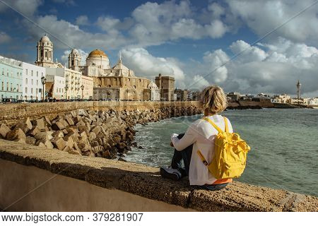 Happy Female Traveler With Backpack Enjoying A Seafront View Of The Old City And Cathedral De Santa