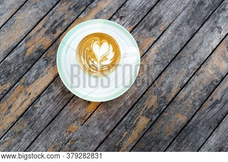 Cup Of Fresh Creamy Cappuccino With Latte Art On Foam. Background Of Wooden Table With Shabby Aged S