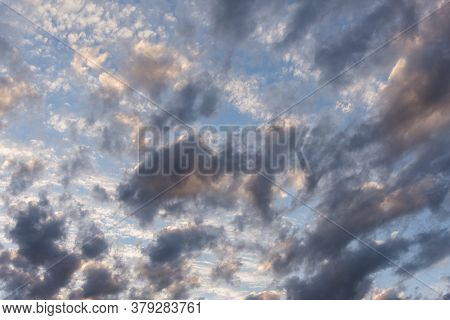 Winter Cloudscape: Cloudy Sunset Sky. Grey And White Clouds Over A Bright Blue Sky