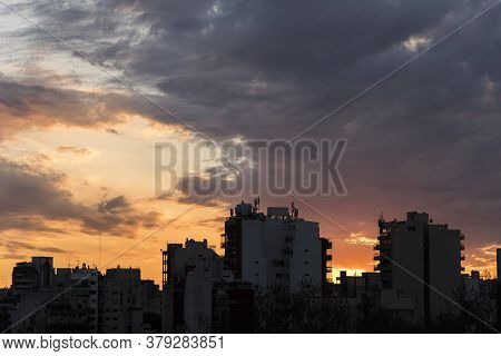 Sunset In Buenos Aires, Argentina. The Silhouette Of Some Buildings In Backlight Contrasts With An O