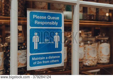 Broadway, Uk - July 07, 2020: Please Queue Responsibly Social Distancing Sign A Window Of A Shop In
