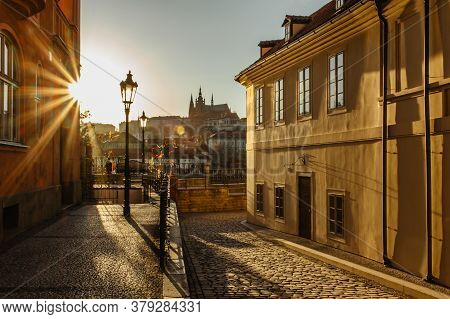Beautiful View Of A Cobblestone Pedestrian Street And Prague Castle With Sun Rays. Tranquil City Sce